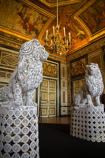 Gardes are two warlike lions in white lace napkins by Franco-Portuguese artist Joana Vasconcelos, the first woman to exhibit in the garden rooms of Versailles. Much of the modern art there seems out of place at times. Although these lions are covered in white lace, at least they are still lions. Photo by Tim Stanley Photography.