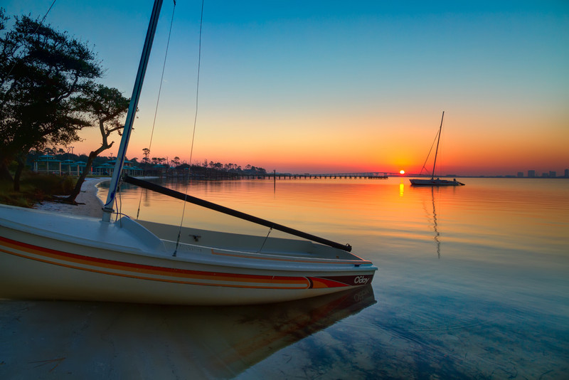 The small sailboat on the beach, combined with the other boat and calm water, made for a nice foreground to what might have been a somewhat plain sunrise. Photo by Tim Stanley Photography.