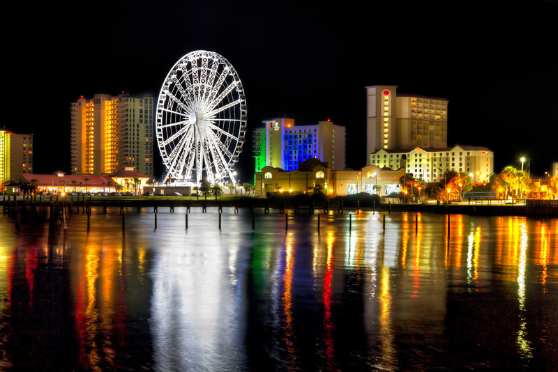 The lights and reflections of the Pensacola skyline on the water shine brightly in the dark of night. Photo by Tim Stanley Photography.