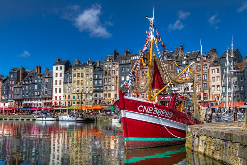 Full of the flavor of France, Honfleur is a photographer's dream, The old, beautiful picturesque port, small shops and cafes contrast the many boats in the harbor. Photo by Tim Stanley Photography.