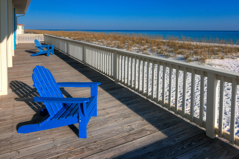 I've come to appreciate the soft breeze, relaxing sound of the surf and a nice deck to kick back and rest, like this large deck with the two blue chairs. Photo by Tim Stanley Photography.