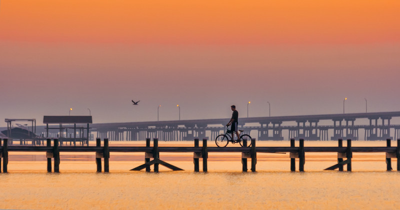 One morning while on vacation, I rose early to capture a sunrise while in Pensacola. I made my way to a surf side park I had found the day before. Much to my surprise, there was already a large group of people jogging and exercising around the park. As the morning brightened, the joggers left, replaced by this lone cyclist. Photo by Tim Stanley Photography.