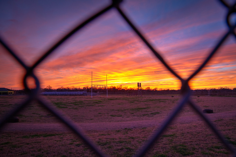 Though the sun was gone, the fence seemed to frame the colorful clouds nicely through this ball field fence. Photo by Tim Stanley Photography.